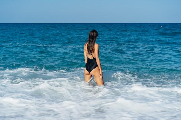 Mooie jonge vrouw die op het overzees rust