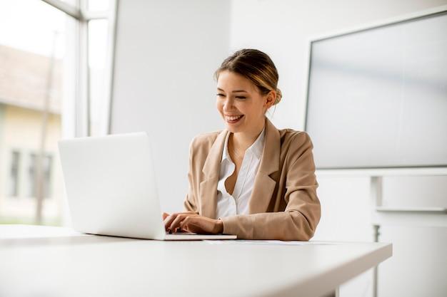 Mooie jonge vrouw die op laptop in heldere kantoor met groot scherm achter haar werkt