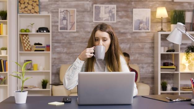 Mooie jonge vrouw die op laptop in kantoor aan huis werkt. jonge freelancer die vanuit huis werkt.