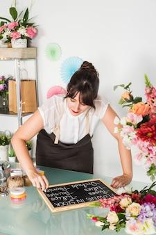 Mooie jonge vrouw die op lei met krijt in bloemenwinkel schrijft