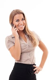 Mooie jonge vrouw die op mobiele telefoon spreekt