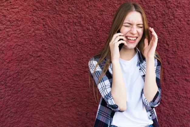 Mooie jonge vrouw die op smartphone met gelukkige gelaatsuitdrukking spreekt