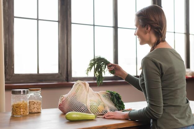 Mooie jonge vrouw die organische kruidenierswinkels neemt uit zak