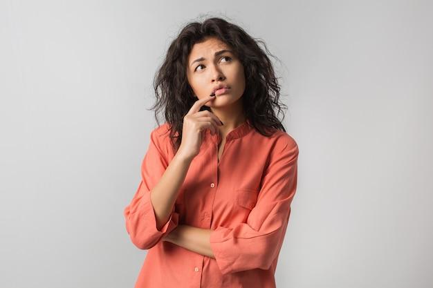 Mooie jonge vrouw die over probleem denkt, verwarde emotie, geïsoleerd, oranje overhemd draagt, hipsterstijl, krullend haar, vinger op lippen houdt, omhoog kijkt, idee heeft