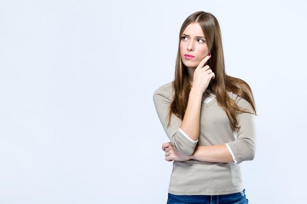 Mooie jonge vrouw die over witte achtergrond denkt.