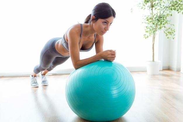 Mooie jonge vrouw die pilate oefening met fitness bal thuis doet.