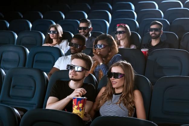 Mooie jonge vrouw die popcorn deelt met haar knappe vriendje tijdens het kijken naar een 3d-film in de bioscoop
