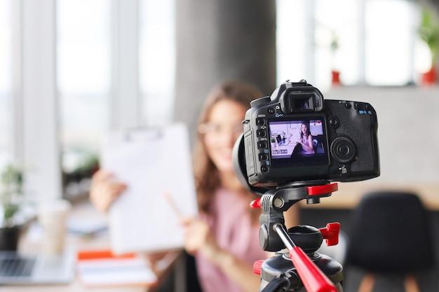 Mooie jonge vrouw die praat en glimlacht terwijl ze een nieuwe video maakt voor haar blog.