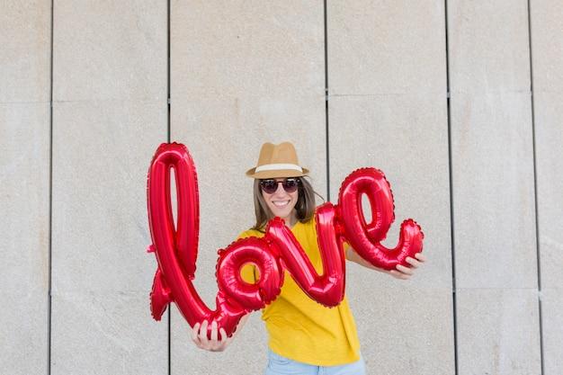 Mooie jonge vrouw die pret in openlucht met een rode ballon met een vorm van het liefdewoord heeft. casual kleding. met hoed en moderne zonnebril. levensstijl buitenshuis