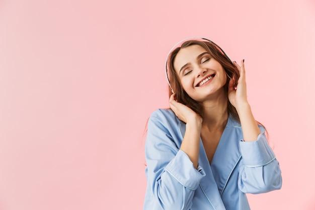 Mooie jonge vrouw die pyjama's draagt die zich geïsoleerd over roze achtergrond bevinden, aan muziek met hoofdtelefoons luisteren