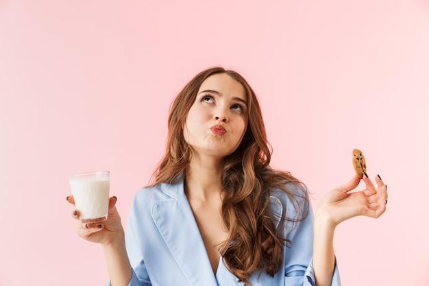 Mooie jonge vrouw die pyjama's draagt die zich geïsoleerd over roze achtergrond bevinden, chocoladekoekjes eten, melk drinken