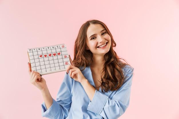 Mooie jonge vrouw die pyjama's draagt die zich geïsoleerd over roze achtergrond bevinden, die menstruatiekalender toont
