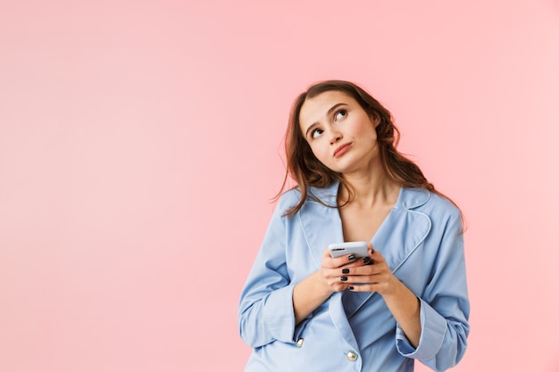 Mooie jonge vrouw die pyjama's draagt die zich geïsoleerd over roze achtergrond bevinden, die mobiele telefoon met behulp van