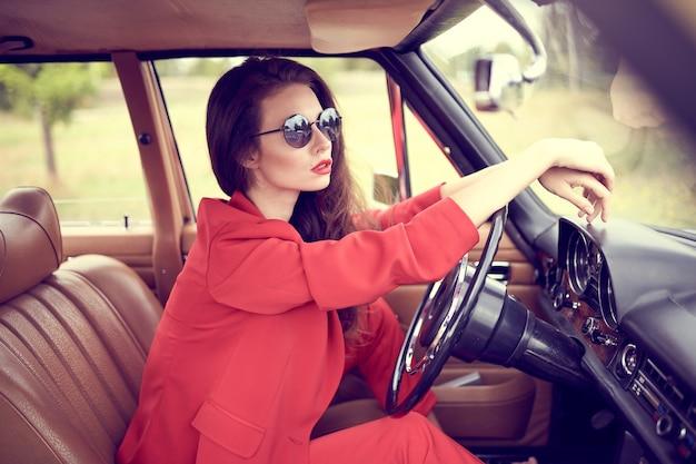 Mooie jonge vrouw die rode kostuum en zonnebril draagt die in retro auto zitten