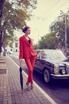 Mooie jonge vrouw die rood kostuum draagt, paraplu vasthoudt terwijl hij dichtbij retro auto staat