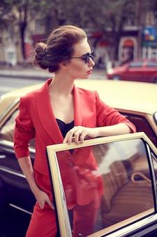 Mooie jonge vrouw die rood kostuum draagt terwijl hij dichtbij retro auto staat