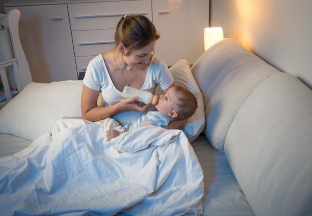 Mooie jonge vrouw die 's nachts melk uit de fles geeft aan haar baby