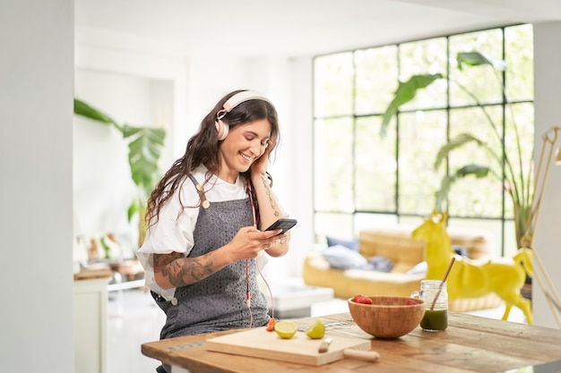 Mooie jonge vrouw die 's ochtends thuis naar muziek luistert met een koptelefoon met een gezond ontbijt
