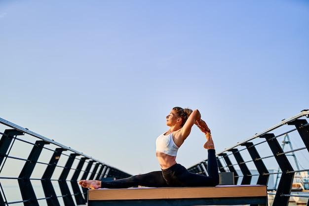 Mooie jonge vrouw die 's ochtends yogaoefeningen doet op de natuur nature