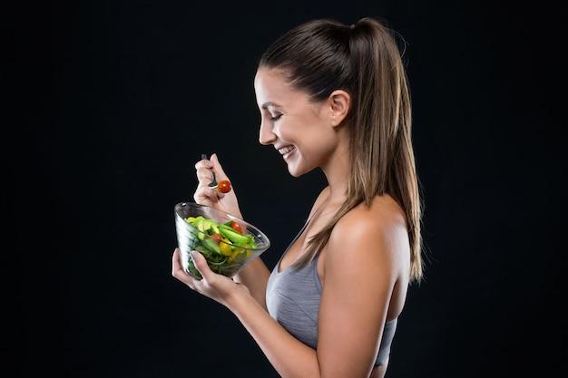 Mooie jonge vrouw die salade over zwarte achtergrond eet.