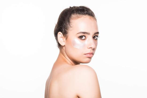 Mooie jonge vrouw die schoonheidsmiddel toepast onder ogen die op witte muur worden geïsoleerd