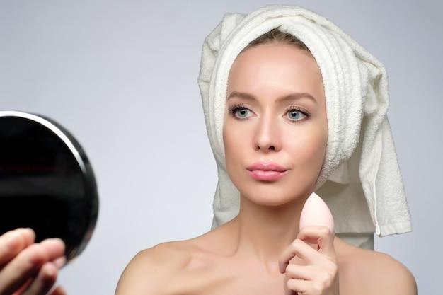 Mooie jonge vrouw die schoonheidsspons gebruikt voor het aanbrengen van foundation voor make-up