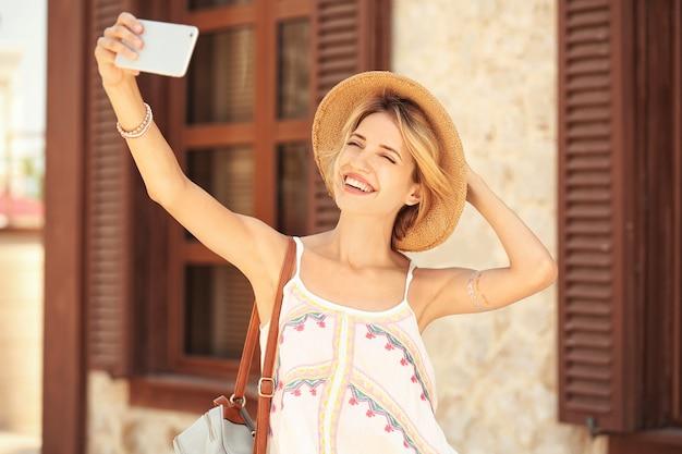 Mooie jonge vrouw die selfie buitenshuis