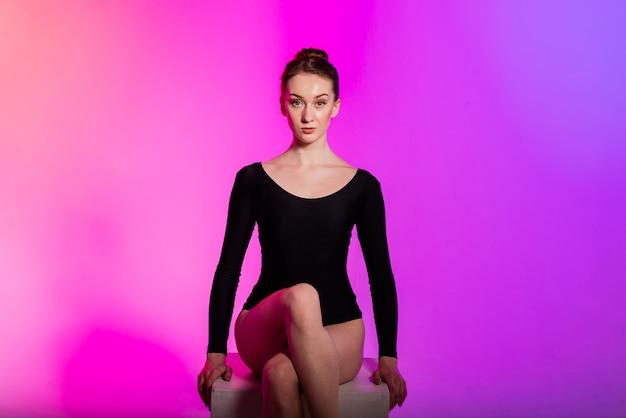 Mooie jonge vrouw die sexy hoge hakken en zwarte kleding draagt tijdens het dansen in een paaldansstudio