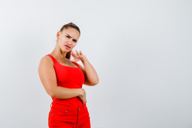 Mooie jonge vrouw die stopgebaar in rood mouwloos onderhemd, broek toont en verward kijkt. vooraanzicht.