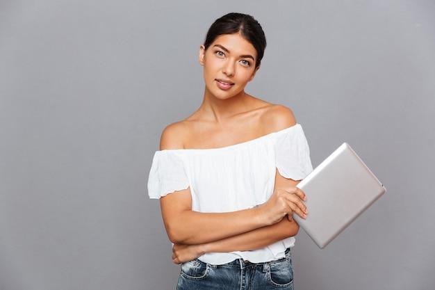 Mooie jonge vrouw die tabletcomputer vasthoudt en naar de voorkant kijkt geïsoleerd op een grijze muur