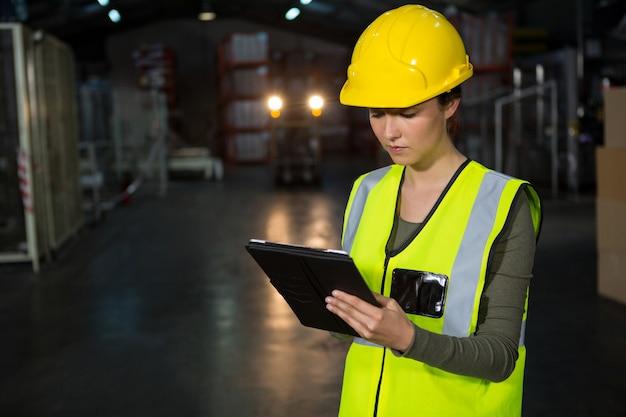 Mooie jonge vrouw die tabletpc in fabriek met behulp van