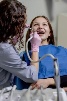 Mooie jonge vrouw die tandonderzoek in de tandartspraktijk doet