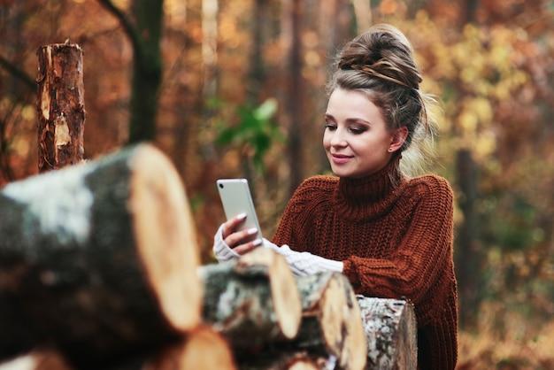 Mooie jonge vrouw die telefoon in bos gebruikt
