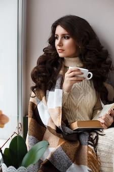 Mooie jonge vrouw die thee drinkt en een boek leest, bedekt met een warme deken, gekleed in een witte gebreide jurk voor het raam.