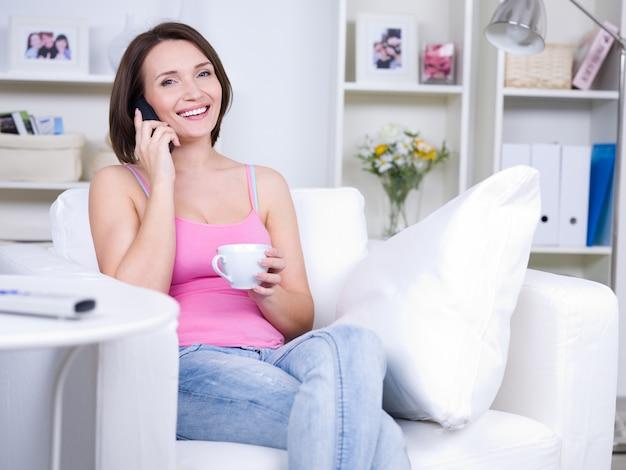 Mooie jonge vrouw die thuis aan de telefoon spreekt - binnenshuis
