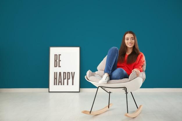 Mooie jonge vrouw die thuis in een comfortabele fauteuil zit