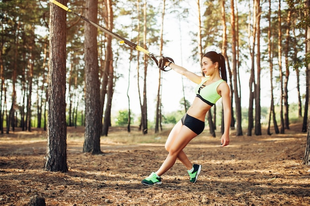 Mooie jonge vrouw die trxoefening met de slinger van de opschortingstrainer in gezonde openlucht doet