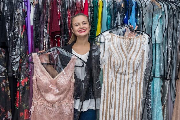 Mooie jonge vrouw die tussen twee roze jurken kiest
