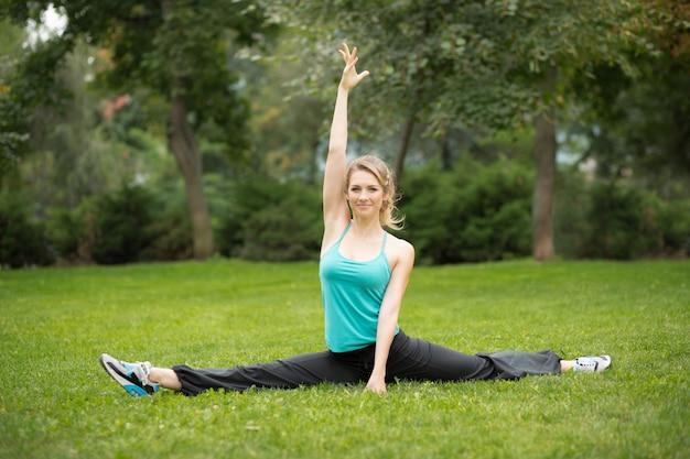 Mooie jonge vrouw die uitrekkende oefeningen in het park doet.