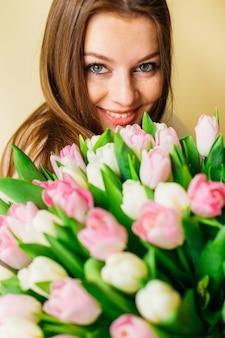 Mooie jonge vrouw die van de lente geniet, die roze bloemen houdt. natuurlijke schoonheid. huidverzorging. lente bruid boeket. fijne vrouwendag.
