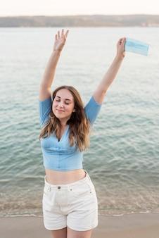Mooie jonge vrouw die van de tijd geniet na quarantaine op het strand