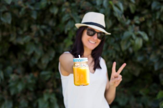 Mooie jonge vrouw die van een jus d'orange in openlucht geniet. groene achtergrond