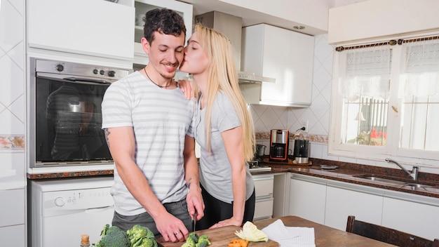 Mooie jonge vrouw die van haar echtgenoot scherpe broccoli in de keuken houden