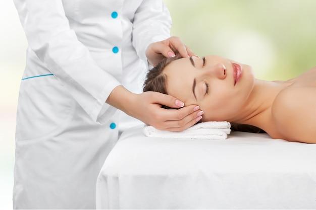 Mooie jonge vrouw die van hoofdmassage in kuuroordcentrum geniet