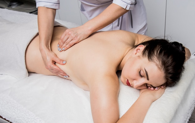 Mooie jonge vrouw die van massage in kuuroordsalon geniet. cosmetologie