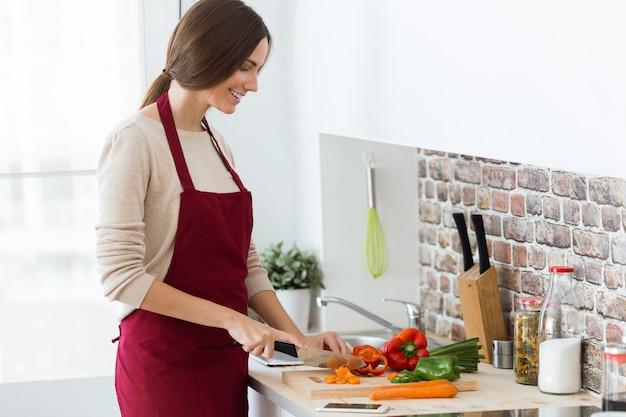 Mooie jonge vrouw die verse groenten in de keuken snijdt.