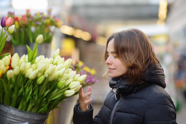 Mooie jonge vrouw die verse tulpen selecteert bij de beroemde bloemenmarkt van amsterdam (bloemenmarkt).
