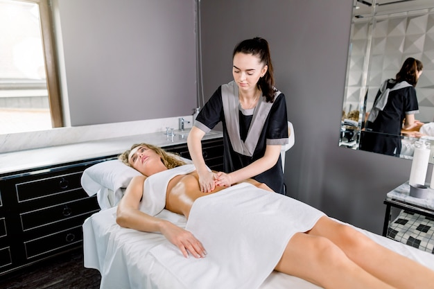 Mooie jonge vrouw die viscerale massage in kuuroordcentrum heeft. jonge vrouwelijke artsentherapeut die handmassage op vrouwelijke buik doen.