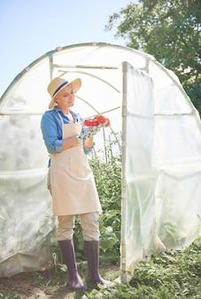 Mooie jonge vrouw die voor haar tuin zorgt