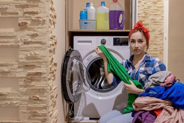 Mooie jonge vrouw die wasserij doet. huiswerk